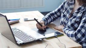 Diseñador gráfico de la mujer que trabaja con la tableta y la pluma digitales del dibujo en un ordenador almacen de video