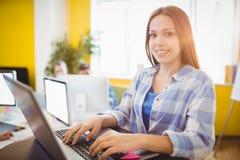 Diseñador gráfico de sexo femenino feliz que trabaja con el ordenador portátil Imagen de archivo