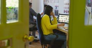 Diseñador gráfico de sexo femenino que escribe en el diario en el escritorio 4k almacen de video