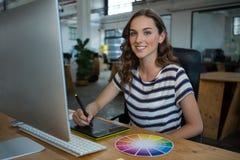 Diseñador gráfico de sexo femenino que usa la tableta de gráficos en el escritorio Fotografía de archivo