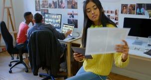 Diseñador gráfico de sexo femenino que usa la tableta digital en la oficina 4k metrajes