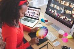 Dise?ador gr?fico de sexo femenino usando muestra del color en el escritorio fotos de archivo libres de regalías
