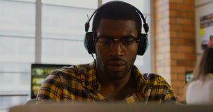 Diseñador gráfico de sexo masculino que escucha la música en el escritorio 4k almacen de video