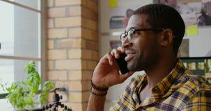 Diseñador gráfico de sexo masculino que habla en el teléfono móvil en el escritorio en la oficina 4k almacen de metraje de vídeo