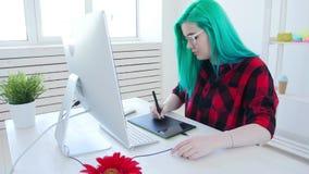Diseñador gráfico joven con el pelo del color que trabaja en el ordenador usando la tableta metrajes