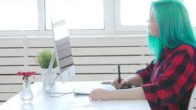 Diseñador gráfico joven con el pelo del color que trabaja en el ordenador usando la tableta almacen de metraje de vídeo