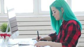 Diseñador gráfico joven con el pelo del color que trabaja en el ordenador usando la tableta almacen de video