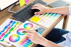 Diseñador gráfico o ratón que se sostiene creativo y hacer sus herramientas del arte de las muestras de la muestra del pantone de fotografía de archivo libre de regalías