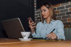 Diseñador gráfico que trabaja con el ordenador portátil y que usa smartphone imagen de archivo libre de regalías