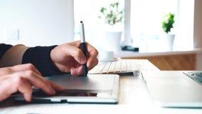 Diseñador gráfico que trabaja con la tableta y la pluma digitales del dibujo metrajes