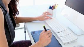 Diseñador gráfico que trabaja en el digitizador en su escritorio almacen de metraje de vídeo