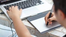Diseñador gráfico que usa la tableta digital y el ordenador en casa offic Imágenes de archivo libres de regalías
