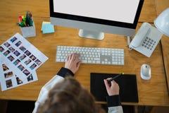 Diseñador gráfico que usa PC de sobremesa y la tableta gráfica Imágenes de archivo libres de regalías
