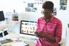 Diseñador gráfico usando el teléfono móvil en el escritorio en oficina foto de archivo libre de regalías