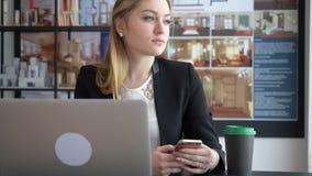 Diseñador hermoso de la mujer que manda un SMS en su smartphone almacen de metraje de vídeo