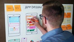 Diseñador joven de UX que desarrolla la disposición responsiva móvil del app almacen de metraje de vídeo