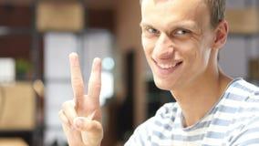 Diseñador joven en la oficina que muestra la muestra de la victoria, realización acertada del proyecto metrajes