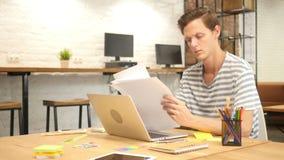 Diseñador joven Reading Paperwork en el escritorio en oficina del desván almacen de metraje de vídeo