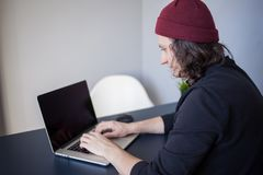 Diseñador para un ordenador portátil, un lugar de trabajo para los freelancers Un hombre joven que se sienta en una tabla fotografía de archivo