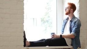Diseñador pensativo Drinking Coffee, sentándose en ventana, pelos rojos y barba almacen de metraje de vídeo