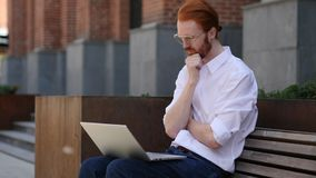 Diseñador pensativo Thinking mientras que trabaja en el ordenador portátil fotografía de archivo libre de regalías