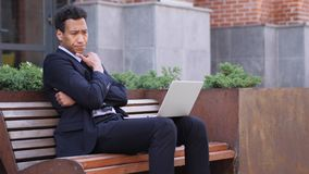 Diseñador pensativo Thinking mientras que trabaja en el ordenador portátil imagen de archivo