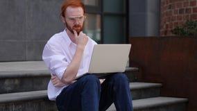 Diseñador pensativo Thinking mientras que trabaja en el ordenador portátil que se sienta cerca de ventana fotos de archivo libres de regalías