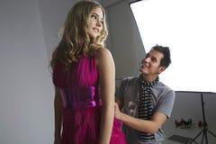 Diseñador que ajusta el vestido del modelo de moda en estudio Foto de archivo