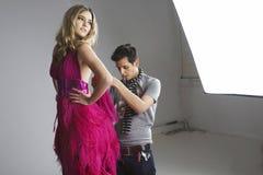 Diseñador que ajusta el vestido en modelo de moda en estudio Imagenes de archivo