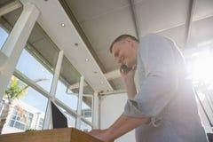 Diseñador que habla en el teléfono elegante mientras que se coloca en el escritorio en oficina fotos de archivo libres de regalías
