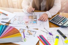 Diseñador que trabaja con el compás sobre plan de la casa imagen de archivo