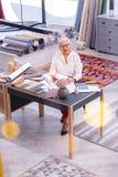 Diseñador que trabaja en el bosquejo que se sienta en engullido con el escritorio de la materia textil fotos de archivo libres de regalías