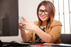 Diseñador que usa un teléfono elegante Foto de archivo libre de regalías