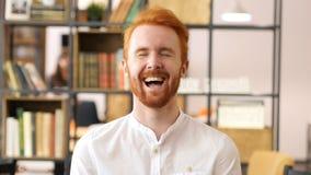 Diseñador rojo Laughing de la barba del pelo en oficina Foto de archivo libre de regalías
