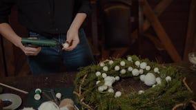Diseñador sonriente lindo joven de la mujer que prepara la guirnalda imperecedera del árbol de la Navidad Fabricante de decoració almacen de metraje de vídeo