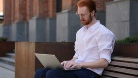 Diseñador Typing en el ordenador portátil mientras que se sienta fuera de oficina almacen de video