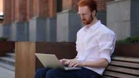 Diseñador Typing en el ordenador portátil mientras que se sienta fuera de oficina imagenes de archivo