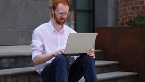 Diseñador Typing en el ordenador portátil mientras que se sienta en las escaleras de la oficina almacen de metraje de vídeo