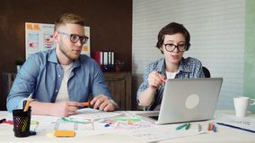 Diseñador web que muestra su concepto del diseñador en el ordenador al compañero de trabajo almacen de video