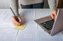 Diseñador web que trabaja en el ordenador portátil y los bosquejos del wireframe del sitio web Foto de archivo libre de regalías