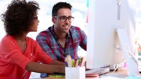 Diseñadores atractivos que trabajan junto en un ordenador