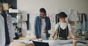 Diseñadores de moda hombre y mujer que trabajan con la tela y que usan smartphone metrajes