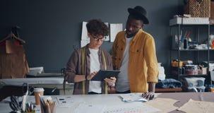Diseñadores de moda modernos que trabajan con la pantalla del touchng de la tableta que habla en estudio metrajes