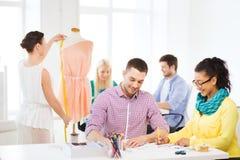 Diseñadores de moda sonrientes que trabajan en oficina Imágenes de archivo libres de regalías