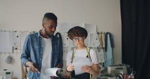 Diseñadores de ropa creativos hombre elegante y mujer que discuten hablar de los bosquejos metrajes