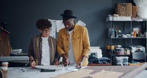 Diseñadores de ropa muchacha e individuo que eligen el color para la nueva ropa que mira los papeles almacen de video