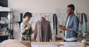 Diseñadores de ropa sonrientes que miden con la medida-cinta que hace notas en cuaderno metrajes