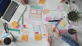Diseñadores de UX que ponen notas de post-it en la disposición del app metrajes