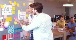 Diseñadores gráficos que leen notas pegajosas