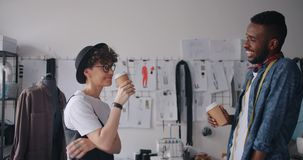 Diseñadores hombre y café para llevar de consumición que habla de relajación de la mujer en estudio almacen de video